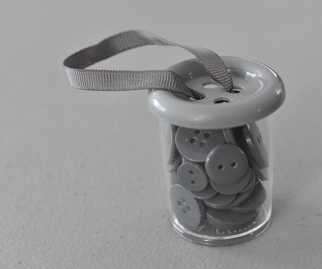 Container of multi-sized grey buttons
