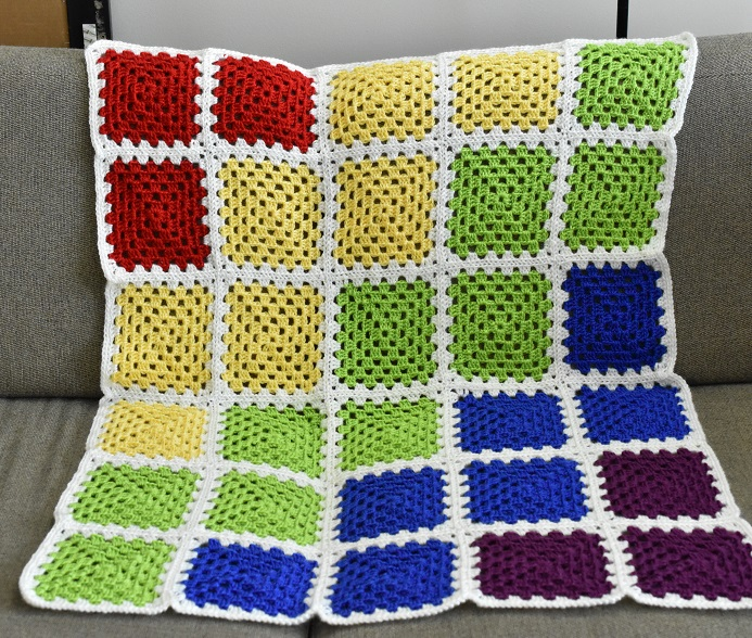 Crocheted granny square rainbow blanket