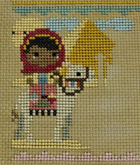 Cross stitch scene of a girl riding a camel past a pyramid